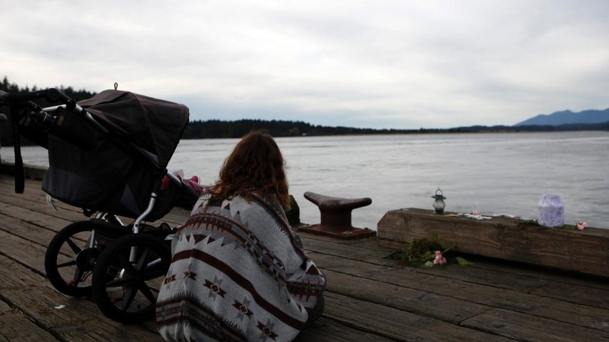 A mourner and her child sit in front of a memorial set with candles and flowers at the First St. dock on Tuesday, Oct. 27, 2015, to remember those involved in the capsizing of the Leviathan II, a whale-watching boat that sunk on Sunday, near Tofino, British Columbia. (Chad Hipolito/The Canadian Press via AP) MANDATORY CREDIT