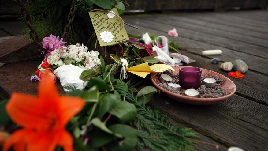 A memorial is set with candles and flowers at the First St. dock on Tuesday, Oct. 27, 2015, to remember those involved in the capsizing of the Leviathan II, a whale-watching boat that sunk on Sunday, near Tofino, British Columbia. (Chad Hipolito/The Canadian Press via AP) MANDATORY CREDIT