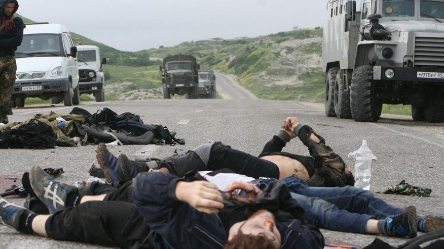 FOR STORY RUSSIA ISLAMIC STATE THREAT Wednesday Oct. 28, 2015 - FILE - In this Thursday, May 9, 2013 file photo, bodies of killed militants lie on a highway at Gubden in Dagestan, Russia. The Russian province of Dagestan, a flashpoint for Islamic violence in the North Caucasus, is feeding hundreds of fighters to the Islamic State in Syria, officials say, and now some are coming back home with experience gained from the battlefield. (Abdula Magomedov/NewsTeam via AP, File)