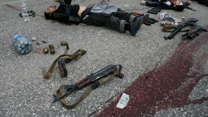 FOR STORY RUSSIA ISLAMIC STATE THREAT Wednesday Oct.28, 2015 - FILE - In this Thursday, May 9, 2013, file photo bodies of killed militants lie surrounded by different kinds of explosives and weapons at Gubden in Dagestan, Russia. The Russian province of Dagestan, a flashpoint for Islamic violence in the North Caucasus, is feeding hundreds of fighters to the Islamic State in Syria, officials say, and now some are coming back home with experience gained from the battlefield.  (Abdula Magomedov/NewsTeam via AP,  File)