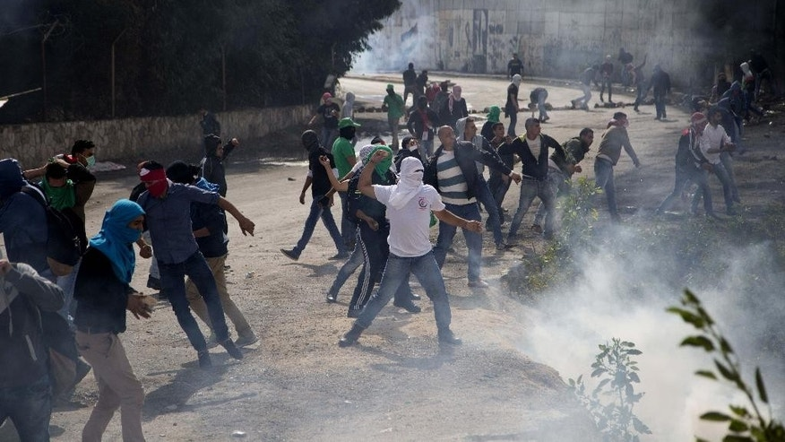 Palestinian students hurl stones at Israeli troops over the separation barrier during clashes following a protest near the Al-Quds University in the West Bank village of Abu Dis, near Jerusalem, Wednesday, Oct. 28, 2015. (AP Photo/Majdi Mohammed)