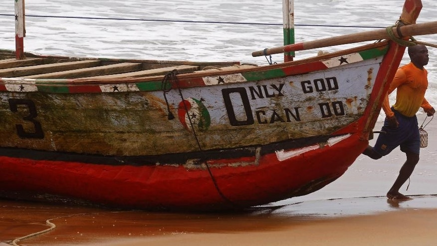 A man that collected ocean water runs past a fishing boat named 'Only God Can Do' at a fishing village renowned as a tourist hot spot visited by French and other tourist yearly in Grand Bassam, Ivory Coast, Tuesday, Oct. 27, 2015.  Ivory Coast voters await result after elections on Sunday as the West African nation held its first presidential election since a disputed vote five years ago. (AP Photo/Schalk van Zuydam)