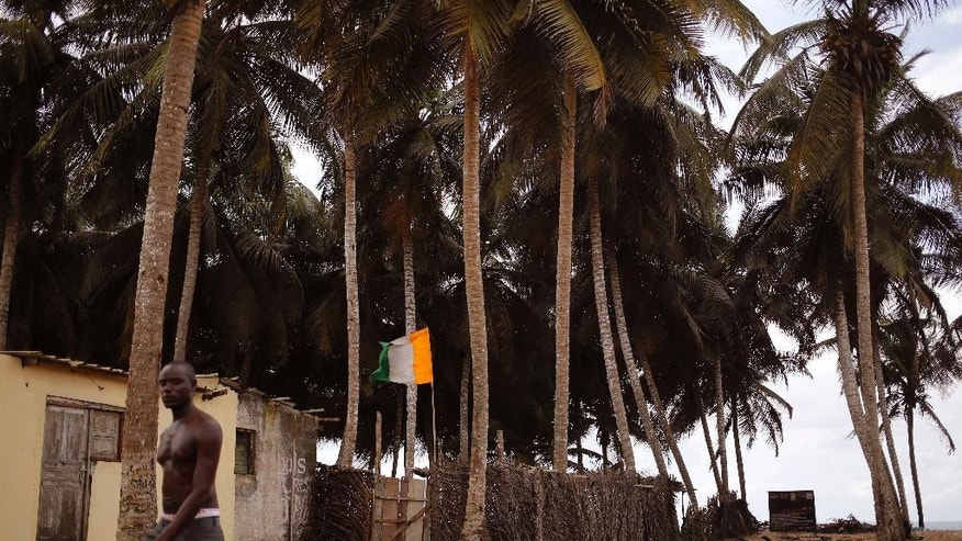 A man, left, passes a home stead, with a Ivory Coast national flag, center, seen  at a fishing village renowned as a tourist hot spot visited by French and other tourist yearly in Grand Bassam, Ivory Coast, Tuesday, Oct. 27, 2015.  Ivory Coast voters await result after elections on Sunday as the West African nation held its first presidential election since a disputed vote five years ago. (AP Photo/Schalk van Zuydam)