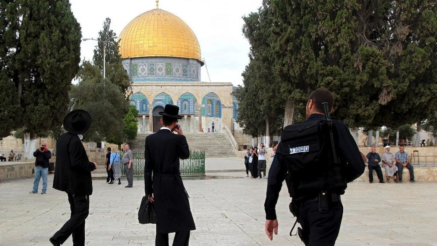 In this Tuesday, Oct. 27, 2015 photo, Israeli policeman escort ultra-Orthodox Jews as they walk past the Dome of the Rock mosque in Jerusalem's most sensitive holy site, a hilltop compound in the Old City that is revered by Jews and Muslims. A new Israeli proclamation vowing to uphold a ban on Jewish prayer at Jerusalem's most sensitive holy shrine should have dealt a blow to the Jewish activists who have spent years fighting for the right to pray at the Muslim site where the ancient Jewish temple once stood. Instead, it has only emboldened them, and they are pledging to step up their attempts to change the decades-old status quo at the site. (AP Photo/Mahmoud Illean)