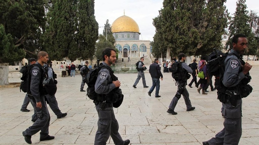 In this Tuesday, Oct. 27, 2015 photo, Israeli policeman escorts Jewish visitors as they walk past the Dome of the Rock mosque in Jerusalem's most sensitive holy site, a hilltop compound in the Old City that is revered by Jews and Muslims. A new Israeli proclamation vowing to uphold a ban on Jewish prayer at Jerusalem's most sensitive holy shrine should have dealt a blow to the Jewish activists who have spent years fighting for the right to pray at the Muslim site where the ancient Jewish temple once stood. Instead, it has only emboldened them, and they are pledging to step up their attempts to change the decades-old status quo at the site. (AP Photo/Mahmoud Illean)