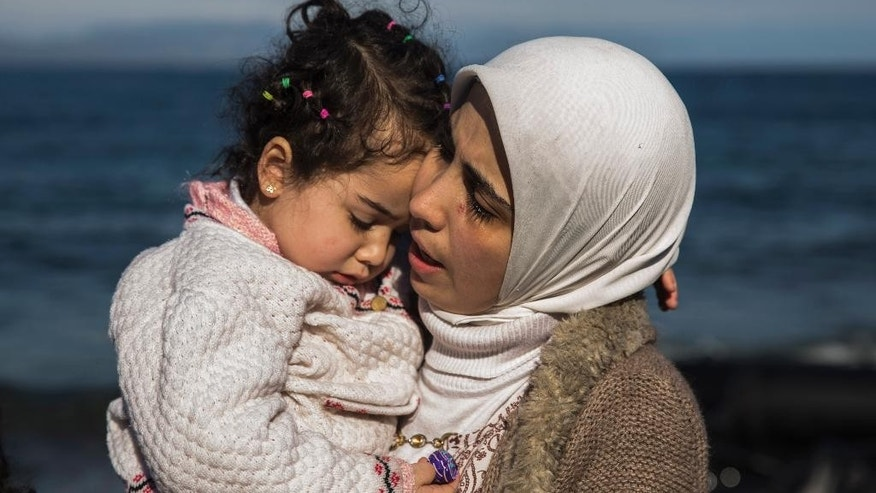 A Syrian mother hugs her child after they arrived from Turkey at the Greek island of Lesbos  on an overcrowded inflatable boat , Tuesday, Oct. 27, 2015. Greece's government says it is preparing a rent-assistance program to cope with a growing number of refugees, who face the oncoming winter and mounting resistance in Europe. (AP Photo/Santi Palacios)