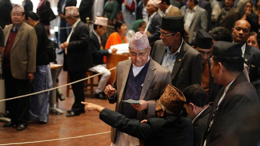 Nepalese Prime Minister Khadga Prasad Oli, center,prepares to cast his vote as lawmakers vote for a new president in Kathmandu, Nepal, Wednesday, Oct. 28, 2015. The prime minister is Nepal's leader, while the president is the ceremonial head.The new constitution adopted last month requires Nepal to name a new president.(AP Photo/Niranjan Shrestha)