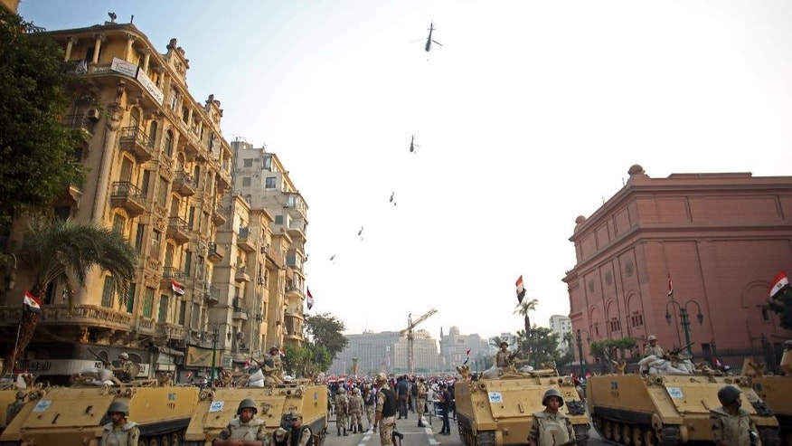 FILE - In this Sunday, Oct. 6, 2013, file photo, Egyptian military helicopters fly overhead as army soldiers stand guard at an entrance to Tahrir Square, in Cairo. The ever-growing, secret defense budgets and poor oversight of militaries in the Middle East make them susceptible to corruption and more vulnerable to extremist violence, a watchdog group warned. (AP Photo/Khalil Hamra, File)
