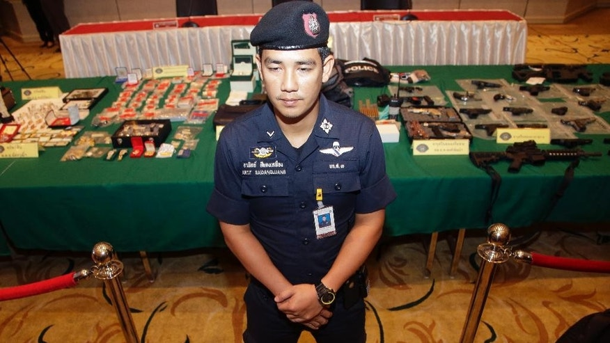 Thai policeman stand guard before a press conference in Bangkok, Thailand, Wednesday, Oct. 28, 2015. Last week a senior police officer and a well-known fortune teller and his assistant were arrested and charged with claiming connections with the royal palace in order to enrich themselves. (AP Photo/Sakchai Lalit)