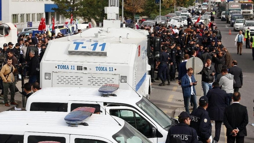 Riot police stand at the entrance as other police officers control some hundreds of protesters outside the headquarters of Koza-Ipek Holding, a business group that owns opposition television stations and newspapers in Ankara, Turkey, Tuesday, Oct. 27, 2017.  The government accuses the movement led by Fethullah Gulen of attempts to destabilize it, and critics denounced the action as a government crackdown on opposition voices ahead of an election Nov. 1.(AP Photo)