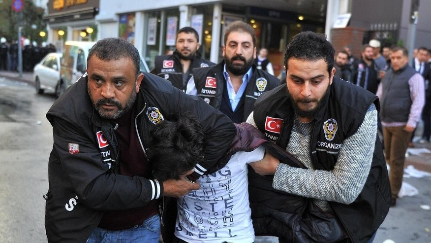 Police detain a protester as they confront protesters near the headquarters of a media company with alleged linked to a government critic, where police enforced a court order to seize the business, in Istanbul, Oct. 28, 2015.  Police in Istanbul carried out the dawn raid at the building, using tear gas and water canons during confrontations with protesters,  Critics denounced the action as a government crackdown on opposition voices ahead of the Nov. 1 election. (Usame Ari / Cihan News Agency via AP) TURKEY OUT