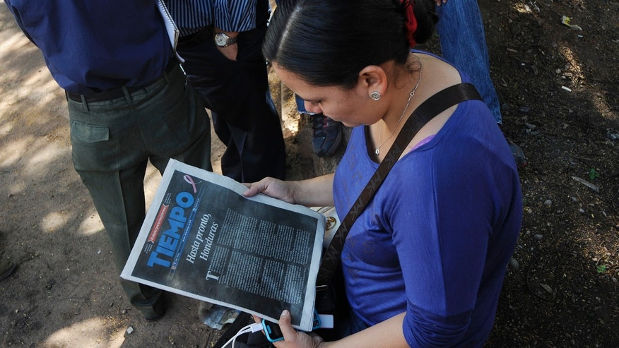 "Xiomara Mairena, journalist at the Diario Tiempo newspaper, reads her paper's last editorial that reads in Spanish: ""So long, Honduras,"" outside of the newspaper's offices in Tegucigalpa, Honduras, Tuesday, Oct. 27, 2015. The Honduran newspaper Tiempo says it is temporarily closing after the government seized businesses belonging to the paper's owners, who are accused in the United States of money laundering. Tiempo has published for 45 years. (AP Photo/Fernando Antonio)"