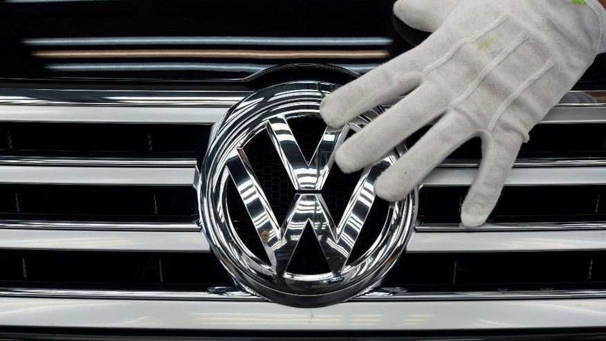FILE -  In this Oct. 23, 2015 file photo a worker touches the logo of Volkswagen AG on a Phaeton in Dresden, Germany. Volkswagen is reporting a loss of 1.67 billion euros (US dollar 1.83 billion) in the third quarter, Wednesday, Oct. 28, 2015, as earnings took a hit from 6.7 billion euros in set-asides for recalls and fines connected to cars rigged to evade U.S. diesel emissions testing. (Ralf Hirschberger/dpa via AP, file)