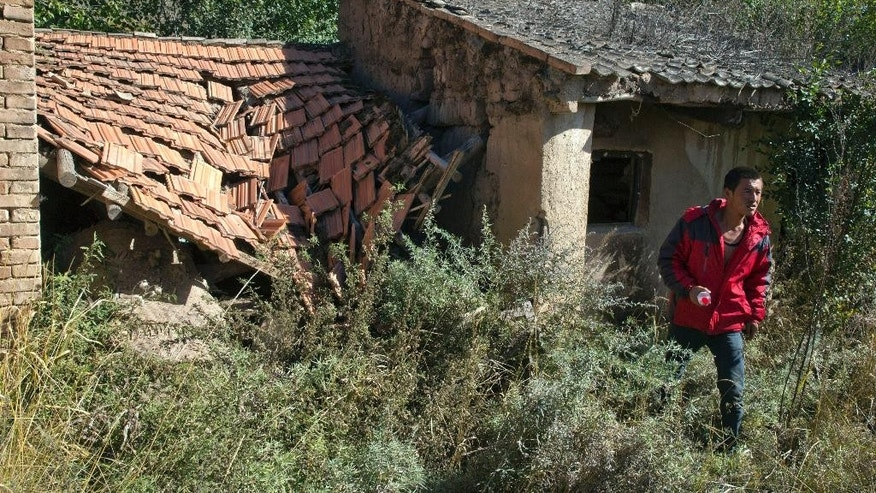In this photo taken Oct. 9, 2015, Yang Jingrong walks through a deserted home of his neighbors who relocated from Dacha village of Xiji county in northwestern China's Ningxia Hui autonomous region. Most former residents of Dacha have moved under a government plan to relocate 350,000 people to lift them out of grinding poverty which, for their region, has been worsened by an increase in average temperatures of 2.2 degrees Celsius (4 degrees Fahrenheit) over the past half-century that leaves the land more parched. (AP Photo/Ng Han Guan)