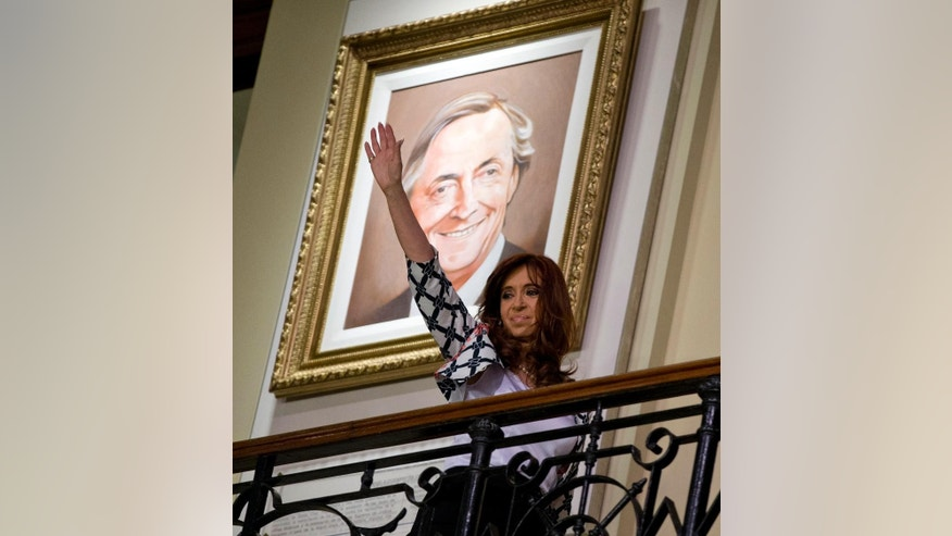 Argentina's President Cristina Fernandez waves at the government house in front of a painting of her late husband Nestor Kirchner in Buenos Aires, Argentina, Thursday, Oct. 29, 2015. Fernandez's chosen successor, presidential candidate Daniel Scioli, will face opposition candidate Mauricio Macri in a presidential runoff election on Nov. 22.  (AP Photo/Natacha Pisarenko)