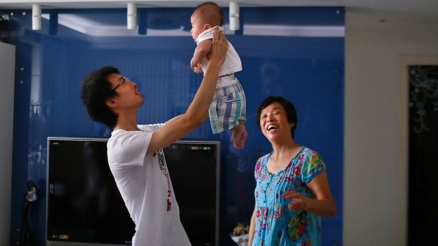 2014: A man holds his son at his apartment in a suburban area of Shanghai.