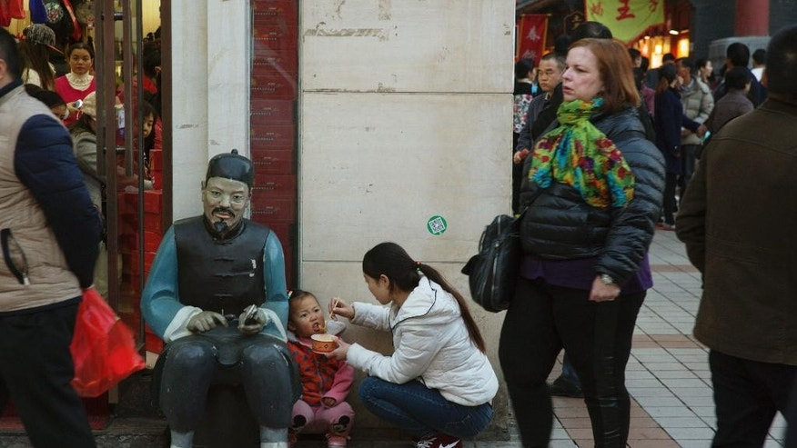 A woman feeds a child in Beijing, China, Thursday, Oct. 29, 2015. China's official Xinhua News Agency says China's ruling Communist Party has decided to abolish the country's one-child policy and allow all couples to have two children. (AP Photo/Ng Han Guan)