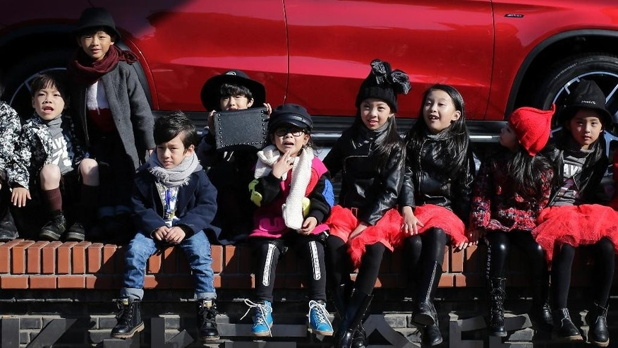 Models for the children's wear fashion show wait outside the venue during the China Fashion Week in Beijing, Thursday, Oct. 29, 2015. China's ruling Communist Party announced Thursday that the country will start allowing all couples to have two children, abolishing an unpopular policy that limited many urban couples to only one child for more than three decades. (AP Photo/Andy Wong)