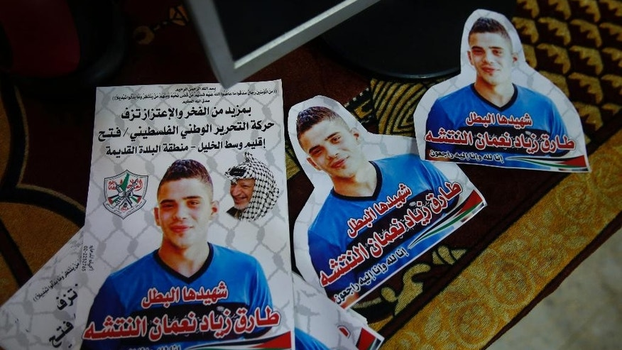 "This photograph made on Wednesday, Oct. 28, 2015, shows posters a 16-year-old Palestinian Tareq Natshe, who stabbed and wounded a soldier Oct. 17, before being shot dead.  at his home in Hebron, West Bank. The West Bank's largest city has become a focal point in Israeli-Palestinian violence, with near-daily deadly confrontations erupting at Israeli army checkpoints that guard enclaves of ultra-nationalist Jewish settlers in the once thriving center of Hebron. The Arabic reads: ""Don't think that God is unaware of what the oppressive actions, there punishment is only delayed till the judgment day. Hamas announces with pride the hero martyr Tareq Zeyad Natshe, who was killed at the Shuhada street, in the center of Hebron, after stabbing one of the occupation's soldiers, Saturday, October 17, 2015."" (AP Photo/Nasser Shiyoukhi)"
