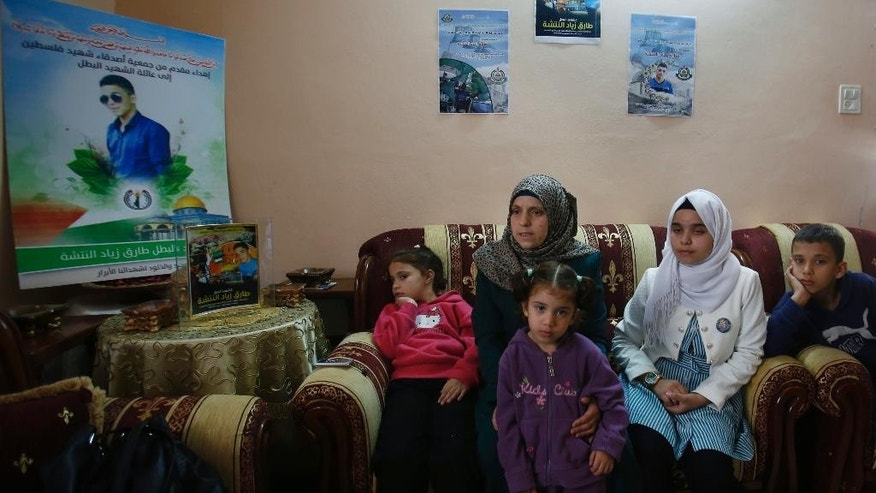 This photograph made on Wednesday, Oct. 28, 2015, shows family of a 16-year-old Palestinian Tareq Natshe, who stabbed and wounded a soldier Oct. 17, before being shot dead. sit underneath posters depicting him at their home in Hebron, West Bank. The West Bank's largest city has become a focal point in Israeli-Palestinian violence, with near-daily deadly confrontations erupting at Israeli army checkpoints that guard enclaves of ultra-nationalist Jewish settlers in the once thriving center of Hebron. (AP Photo/Nasser Shiyoukhi)