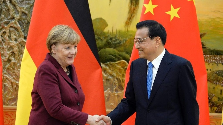 German Chancellor Angela Merkel, left, shakes hands with Chinese Premier Li Keqiang after their press conference at the Great Hall of the People in Beijing Thursday, Oct. 29, 2015. (Muneyoshi Someya/Pool Photo via AP)
