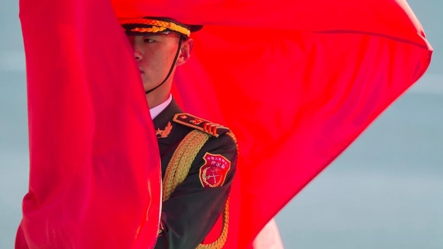 A member of a Chinese honor guard holds a flag before a welcome ceremony for German Chancellor Angela Merkel held outside the Great Hall of the People in Beijing, China, Thursday, Oct. 29, 2015.(AP Photo/Ng Han Guan)