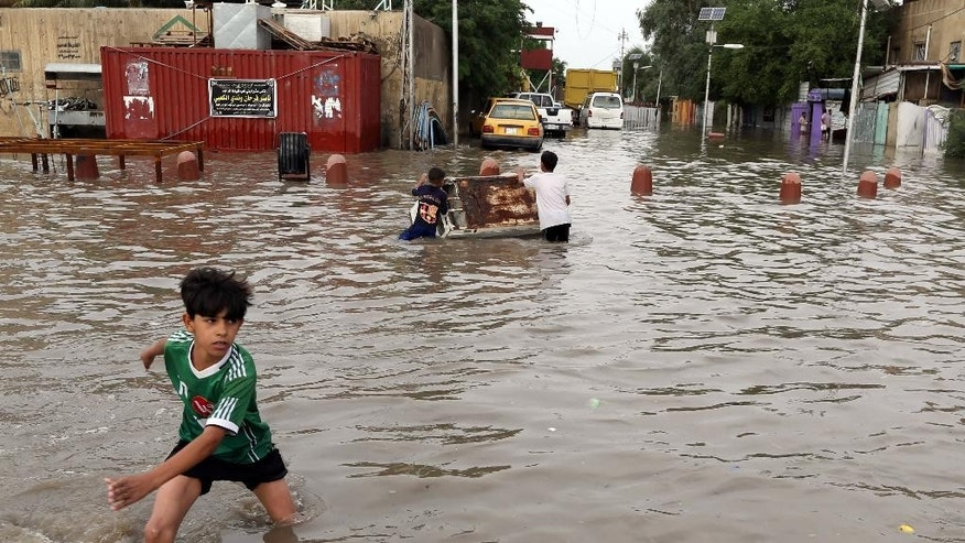 Iraqi boys make their way through a flooded street after heavy rain fell in Baghdad, Iraq, Thursday, Oct. 29, 2015. Rain storms began late day Wednesday and continued through the morning Thursday, dumping heavy rain on the Iraqi capital and across the country. The Iraqi government declared Thursday a holiday to ease the burden on people who may otherwise struggle to get to work. (AP Photo/Karim Kadim)