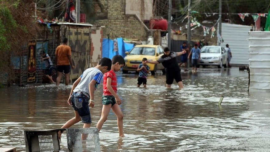 Iraqis make their way through a flooded street after heavy rain fell in Baghdad, Iraq, Thursday, Oct. 29, 2015. Rain storms began late day Wednesday and continued through the morning Thursday, dumping heavy rain on the Iraqi capital and across the country. The Iraqi government declared Thursday a holiday to ease the burden on people who may otherwise struggle to get to work. (AP Photo/Karim Kadim)