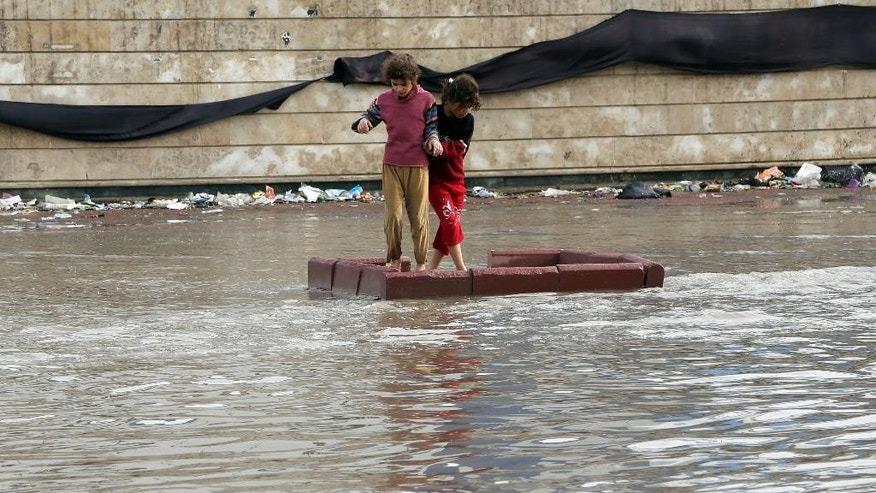 Iraqi girls make their way through a flooded street after heavy rain fell in Baghdad, Iraq, Thursday, Oct. 29, 2015. Rain storms began late day Wednesday and continued through the morning Thursday, dumping heavy rain on the Iraqi capital and across the country. The Iraqi government declared Thursday a holiday to ease the burden on people who may otherwise struggle to get to work. (AP Photo/Karim Kadim)