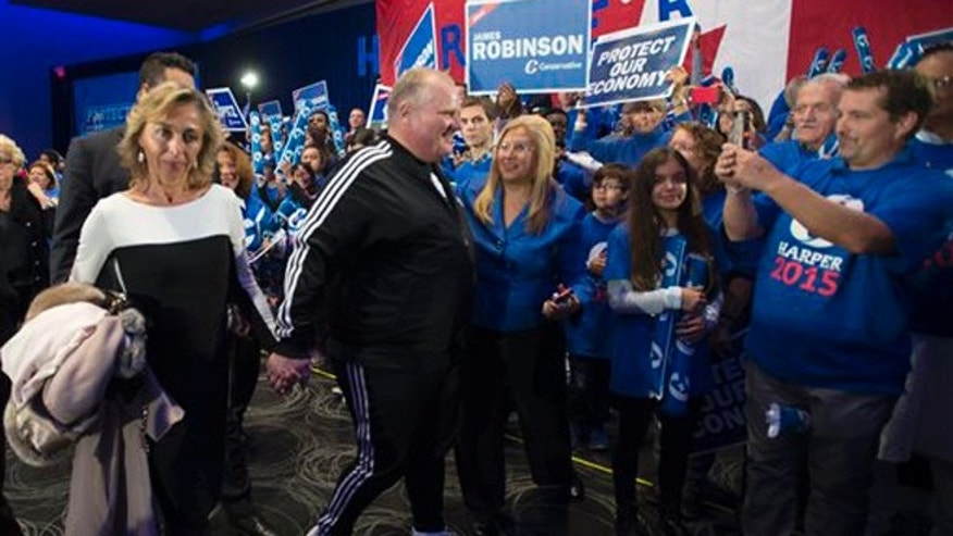 Oct. 17, 2015: Former Toronto Mayor Rob Ford, center, accompanied by wife, Renata, left, leaves a campaign rally following a speech from Conservative Leader, Prime Minister Stephen Harper in Toronto.