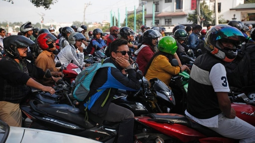 FILE- In this Sept. 28, 2015 file photo, Nepalese motorists wait for their turn to fill fuel on their motorbikes at a fuel pump run by the Nepalese army in Kathmandu, Nepal. Fuel-starved Nepal has signed an agreement with China to provide gasoline, diesel and cooking gas, after India restricted its supplies as a result of ongoing political protests in the Himalayan nation, officials said Thursday.(AP Photo/Niranjan Shrestha, file)