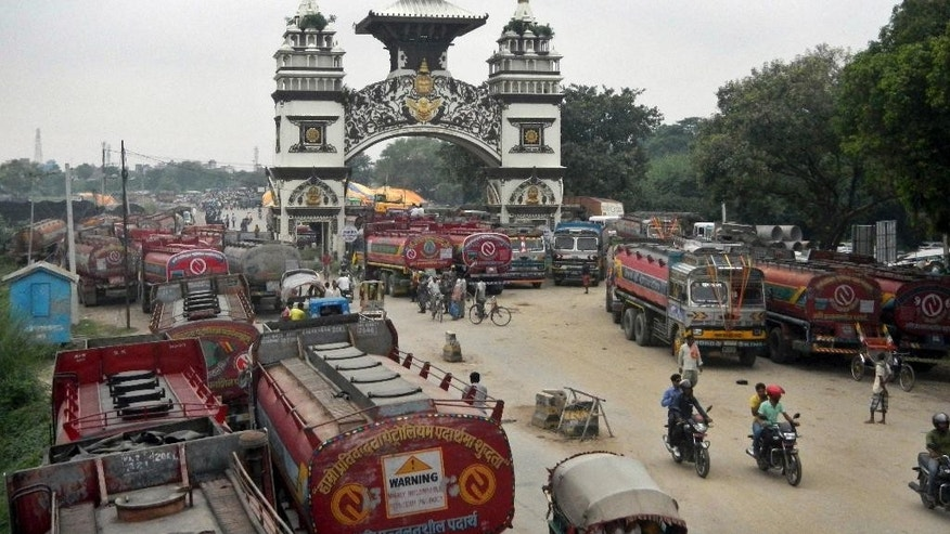 FILE- In this Sept. 24, 2015 file photo, Nepalese oil tankers and commercial trucks stand stranded near a gate that marks the Nepalese border with India, in Birgunj, Nepal. Fuel-starved Nepal has signed an agreement with China to provide gasoline, diesel and cooking gas, after India restricted its supplies as a result of ongoing political protests in the Himalayan nation, officials said Thursday. (AP Photo/Ram Sarraf, file)