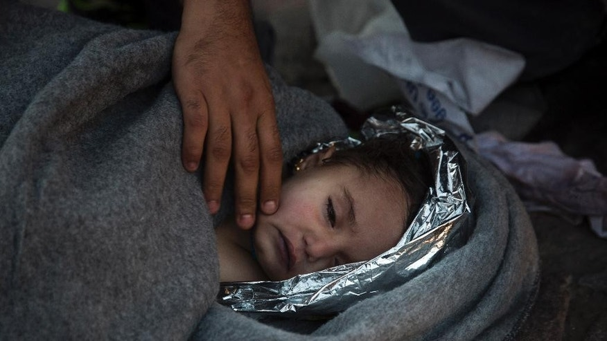 Paramedics and doctors care for a baby girl after a boat with refugees and migrants sunk while was crossing the Aegean sea from Turkey to the Greek island of Lesbos on Wednesday, Oct. 28, 2015. The condition of the child is not known. A 7-year-old boy died off Lesbos, where most migrants land, while a 12-month-old girl was in critical condition in hospital from the same boat accident. Greek authorities said Wednesday that at least five people, including four children, have drowned as thousands of refugees and economic migrants continued to head to the Aegean Sea islands in frail boats from Turkey, in worsening weather. (AP Photo/Santi Palacios)