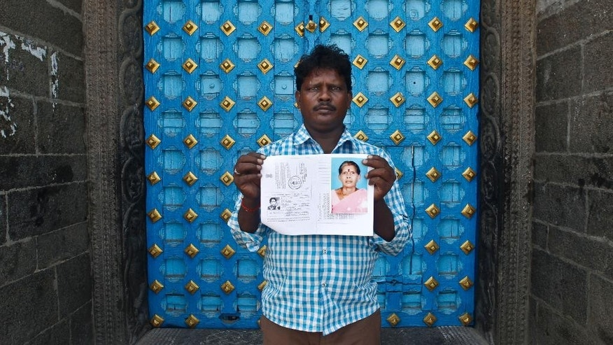 In this Saturday, Oct. 24, 2015, photo, Mohan Munirathinam, son of Kasthuri Munirathinam, displays his mother's photograph and a copy her employment documents in Chennai, India. Kasthuri Munirathinam, a 55-year-old mother of four, worked as a live-in maid in Saudi Arabia. On Sept. 29, just a few weeks after arriving in the kingdom, she tried to escape from her employer's house, using two of her saris to fashion a rope and climb from a third-floor window. Kasthuri lost most of her right arm and is now in a hospital. (AP Photo/Arun Sankar K.)