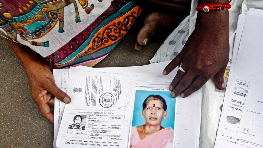 In this Saturday, Oct. 24, 2015, photo, relatives of Kasthuri Munirathinam display a photo of her and copies of her employment documents, in Chennai, India. Munirathinam, a 55-year-old mother of four, worked as a live-in maid in Saudi Arabia. On Sept. 29, just a few weeks after arriving in the kingdom, she tried to escape from her employer's house, using two of her saris to fashion a rope and climb from a third-floor window. Munirathinam lost most of her right arm and is now in a hospital. (AP Photo/Arun Sankar K.)
