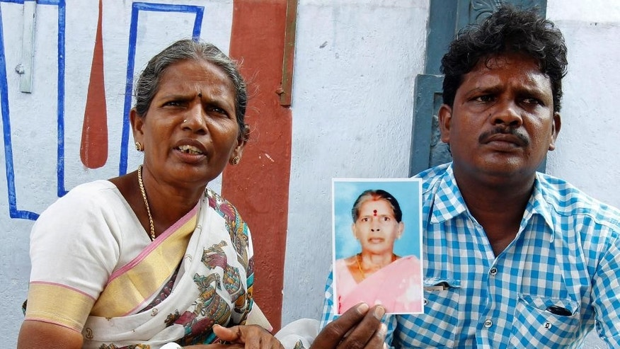 In this Saturday, Oct. 24, 2015, photo, Malliga, sister, and Mohan, son of Kasthuri Munirathinam, display his mother's photograph in Chennai, India. Kasthuri, a 55-year-old mother of four, worked as a live-in maid in Saudi Arabia. On Sept. 29, just a few weeks after arriving in the kingdom, she tried to escape from her employer's house, using two of her saris to fashion a rope and climb from a third-floor window. Kasthuri lost most of her right arm and is now in a hospital. (AP Photo/Arun Sankar K.)
