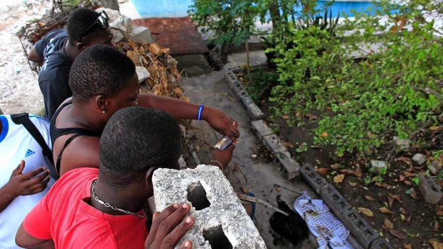People looks at burned ballots over a wall over a wall on the backyard of an abandoned house in the neighborhood of Delmas 41 in Port-au-Prince, Haiti, Thursday, Oct. 29, 2015.  Former Sen. Moise Jean-Charles, of the Petit Dessalines faction and one of Haiti's top presidential candidates insists that ballots checked with his name are being destroyed or discarded, prompting supporters to burn tire barricades in parts of the country's capital. With official preliminary results still days away, his supporters claim they discovered partially burned ballots in Port-au-Prince and say ballots have gone missing elsewhere.(AP Photo/Ricardo Arduengo)