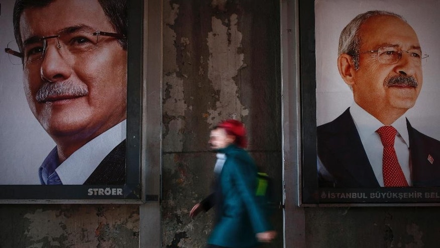 In this Tuesday, Oct. 27, 2015, photo a woman walks past election banners with pictures of Turkey's main opposition Republican People's Party leader Kemal Kilicdaroglu, left, and Turkish Prime Minister Ahmet Davutoglu, the leader of the Justice and Development Party (AKP), in Istanbul. The election is a redo of June elections in which the ruling AKP, stunningly lost its majority. Turkish President Recep Tayyip Erdogan called for new elections after Davutoglu failed to form a coalition with any of the three opposition parties represented in parliament. (AP Photo/Emrah Gurel)