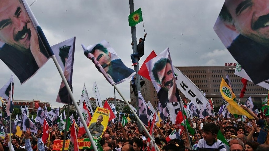 FILE - In this June 8, 2015, file photo, supporters of the pro-Kurdish Peoples' Democratic Party (HDP) cheer as others wave flags of imprisoned Kurdish rebel leader Abdullah Ocalan during a rally in Istanbul. As extremist violence and political uncertainty cast a shadow over Turkey, voters are looking for Nov. 1. 2015, parliamentary elections to usher in stability. The election is a redo of June elections in which the ruling Justice and Development Party, or AKP, stunningly lost its majority. The ballot comes at a sensitive time for Turkey, a key Western ally that has major issues to navigate. (AP Photo/Lefteris Pitarakis, file)