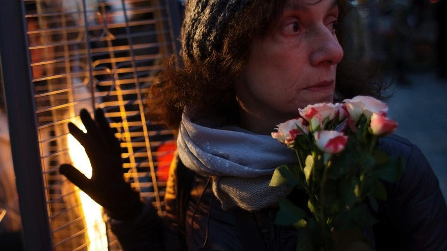 Maria Arutyunian, 59, warms hersef as she waits to light candles and read out names of victims of Soviet dictator Josef Stalin's purges at the Solovky Stone monument in Lubyanka Square, in Moscow, Russia, Thursday, Oct. 29, 2015. On the eve of the Day of Victims of Political Repressions, marked in Russia on Oct. 30, people gather at the memorial, a giant slab of stone taken from a Soviet labor camp in the Solovky Islands, to commemorate the thousands of victims of Soviet-era political repressions. (AP Photo/Ivan Sekretarev)
