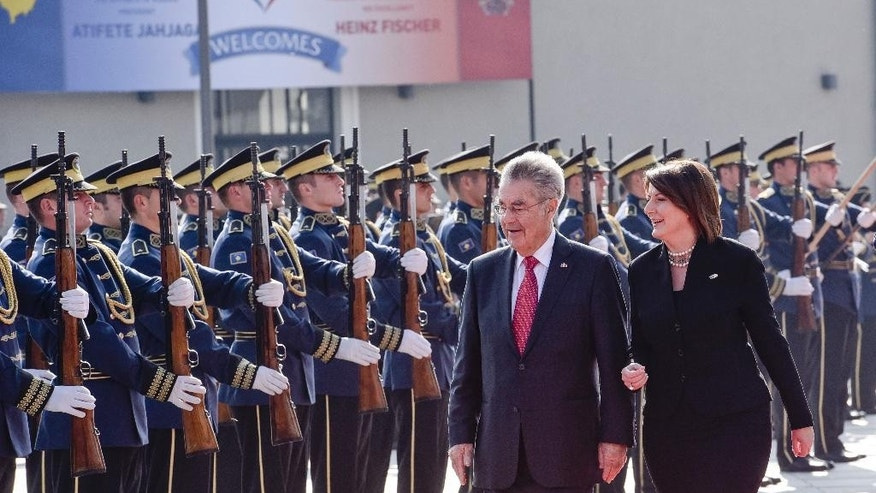 Kosovo President Atifete Jahjaga, right, flanked by Austrian President Heinz Fischer inspecting the honour guard of the Kosovo Security Force, during a welcoming ceremony in Kosovo capital Pristina on Wednesday, Oct. 28, 2015. The Austrian President Heinz Fischer is in a two-day official visit in Kosovo. (AP Photo/Visar Kryeziu)
