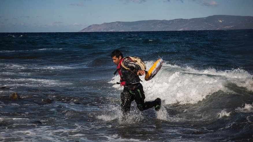 A refugee arrives in bad weather after crossing the Aegean sea from Turkey to the  Greek island of Lesbos on a dinghy , Wednesday, Oct. 28, 2015. The Greek coast guard said it rescued 242 refugees or economic migrants off the eastern island of Lesbos Wednesday after the wooden boat they traveled in capsized, leaving at least three dead on a day when another 8 people drowned trying to reach Greece.(AP Photo/Santi Palacios)