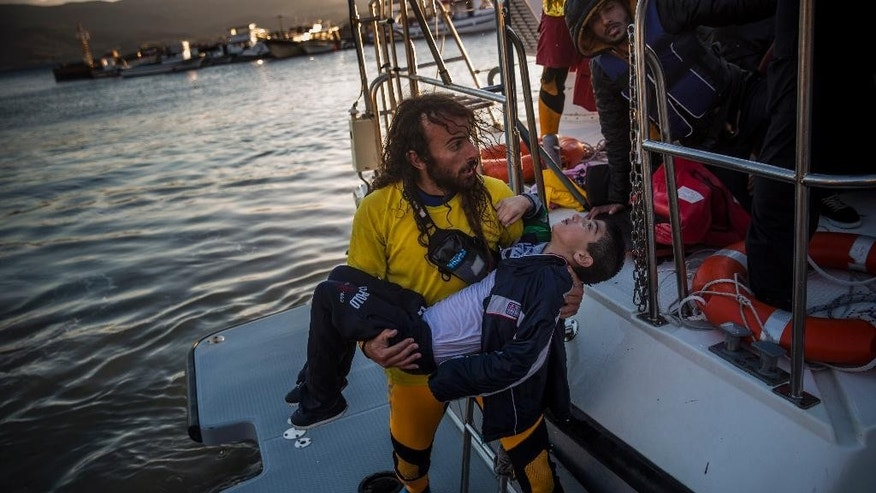 A volunteer carries a young boy after a boat with refugees and migrants sank while crossing the Aegean sea from Turkey to the Greek island of Lesbos, on Wednesday, Oct. 28, 2015.  The condition of the child is not known. The Greek coast guard said it rescued 242 refugees or economic migrants off the eastern island of Lesbos Wednesday after the wooden boat they traveled in capsized, leaving at least three dead on a day when another 8 people drowned trying to reach Greece. (AP Photo/Santi Palacios)