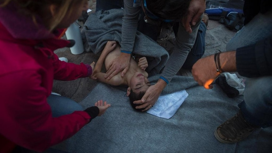Paramedics and doctors try to revive a baby after a boat with refugees and migrants sunk while was crossing the Aegean sea from Turkey to the Greek island of Lesbos on Wednesday, Oct. 28, 2015. The condition of the child is not known. A 7-year-old boy died off Lesbos, where most migrants land, while a 12-month-old girl was in critical condition in hospital from the same boat accident. Greek authorities said Wednesday that at least five people, including four children, have drowned as thousands of refugees and economic migrants continued to head to the Aegean Sea islands in frail boats from Turkey, in worsening weather. (AP Photo/Santi Palacios)