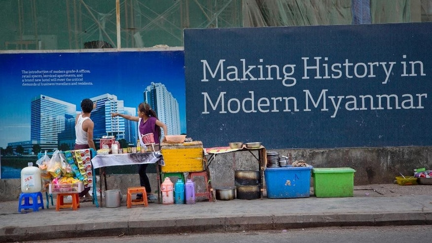 In this Dec. 3, 2014 photo, sidewalk restaurant operators catering to construction workers outside of a construction site point their fingers at a photograph of the proposed building in Yangon, Myanmar. After Myanmar's military installed a civilian government in 2010, foreign investors rushed to set up factories in disused industrial zones and property developers began building luxury housing estates as the long-isolated Southeast Asian economy opened for business. (AP Photo/Gemunu Amarasinghe)