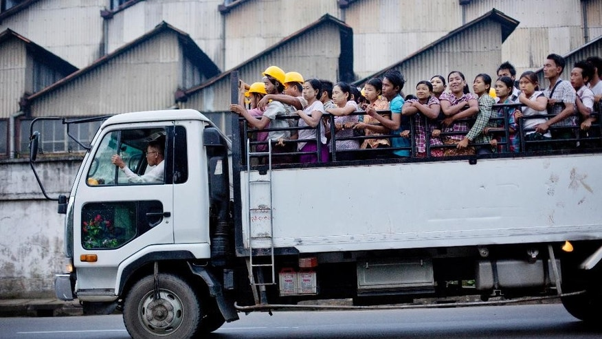 In this Oct. 3, 2014 photo, day laborers traveling in the back of a truck pass a abandoned government owned factory on their way to a construction site in Yangon, Myanmar. After Myanmar's military installed a civilian government in 2010, foreign investors rushed to set up factories in disused industrial zones and property developers began building luxury housing estates as the long-isolated Southeast Asian economy opened for business.(AP Photo/Gemunu Amarasinghe)