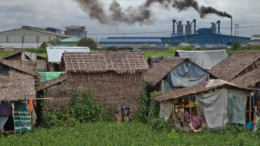 In this Oct. 10, 2015 photo, children peek out from a window of a house built over a creek in front of the Hlaing Tharyar industrial zone outside Yangon, Myanmar. Though Myanmar's growth is over 8.5 percent, and foreign direct investment topped $8 billion in this year, more than a third of Myanmar's 51.4 million people still live on less than $1.25 a day. Their reality is urban slums dominated by gangs, factories paying workers barely enough to get by, and a near absence of public services. (AP Photo/Gemunu Amarasinghe)