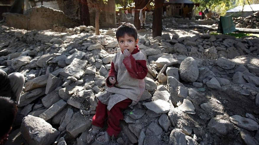A child eats peanuts as he sits on the rubble of a destroyed house caused by Monday's earthquake in Chitral town, northern Pakistan, Thursday, Oct. 29, 2015. People in the Pakistani town of Chitral, one of the closest to the quake's epicenter, say Thursday they are too poor to rebuild their homes and need government help. Repairs are needed urgently, as snow is already falling on nearby mountains. (AP Photo/Anjum Naveed)