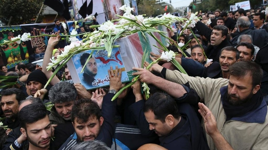 "Iranian mourners carry the flag draped coffin of Abdollah Bagheri Niaraki, a onetime bodyguard of former President Mahmoud Ahmadinejad who was killed while fighting in Aleppo in Syria, during his funeral service in front of his home in downtown Tehran, Iran, Thursday, Oct. 29, 2015. Iran's semi-official Fars news agency reported last Friday that Niaraki was killed while fighting alongside Syrian government forces against ""terrorists"" in the northern city of Aleppo. Iran is a longtime ally of Syrian President Bashar Assad and has provided crucial economic and military backing throughout the uprising and subsequent civil war. Iran says it has sent military advisers to Syria but no combat troops. (AP Photo/Vahid Salemi)"