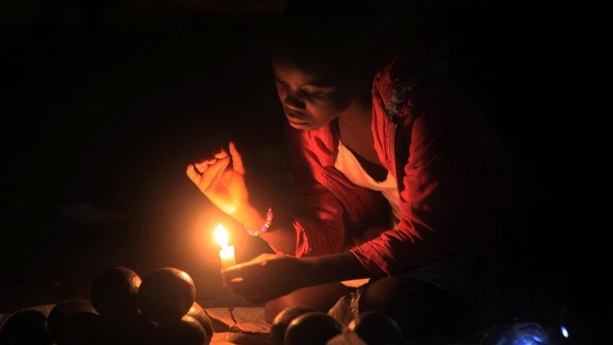 In this photo taken Wednesday Sept. 2015 a woman uses candle light as she sells fruit on a sidewalk in Harare, Zimbabwe. The normal rains did not fall, which caused water levels to drop in dams that produce electricity, so local people and businesses across Zimbabwe and Zambia are suffering power black-outs for up to 48-hours at a time.  Some traditional chiefs blame an angry river god, but the government blames the lack of rain, and work to expand the Kariba power station will not be complete for at least three years, said Partson Mbiriri, permanent secretary in Zimbabwe's ministry of energy and power development. (AP Photo/Tsvangirayi Mukwazhi)